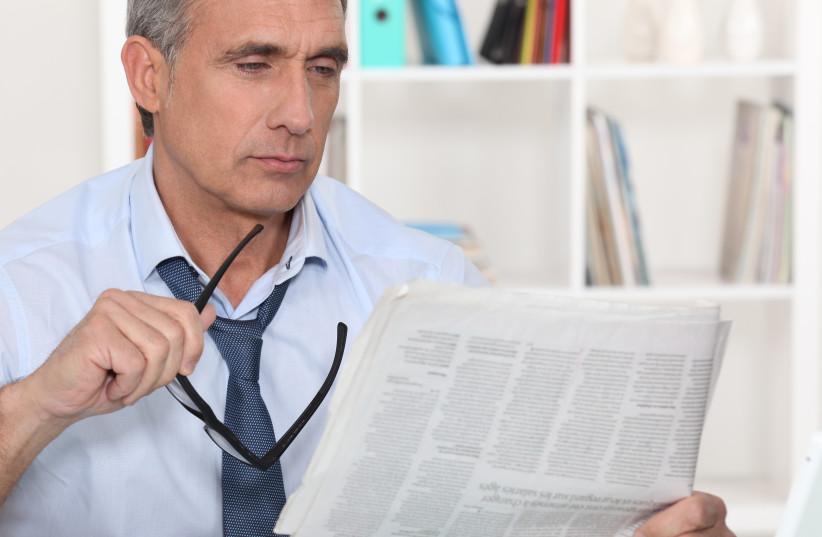 A man reading a paper (photo credit: INGIMAGE)
