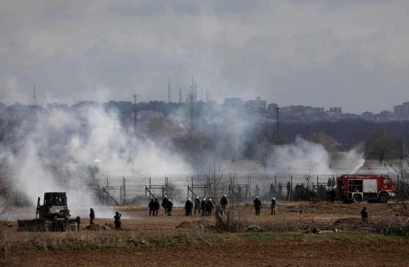 Greek soldiers and riot police officers stand amid clouds of tear gas near Turkey's Pazarkule border crossing, in Kastanies, Greece March 7, 2020 (photo credit: REUTERS/FLORION GOGA)
