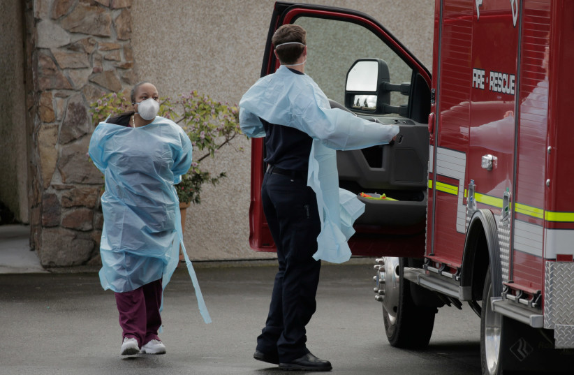 A nursing home worker and a medic put on personal protective equipment while preparing to transport a patient into an ambulance at the Life Care Center of Kirkland, the long-term care facility linked to several confirmed coronavirus cases in the state, in Kirkland, Washington, US. (photo credit: REUTERS)