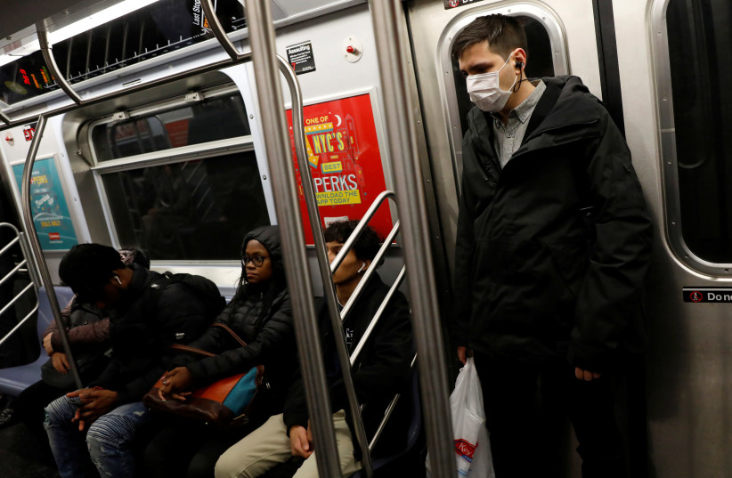 A man in a face mask rides the subway in Manhattan, New York City, after further cases of coronavirus were confirmed in New York, U.S., March 5, 2020. (photo credit: ANDREW KELLY / REUTERS)