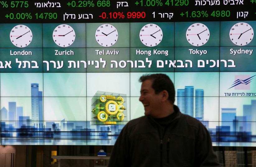 A man stands in front of an electronic board displaying market data at the Tel Aviv Stock Exchange, in Tel Aviv, Israel (photo credit: REUTERS/BAZ RATNER)