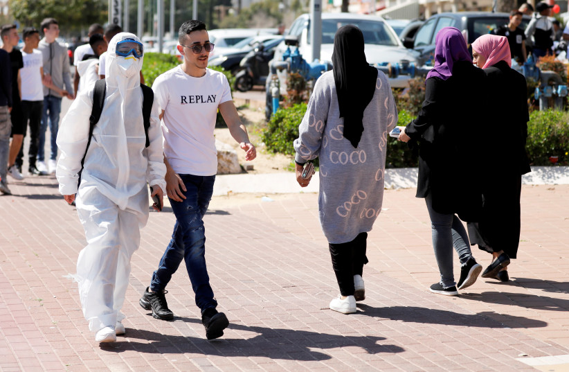 A teenager wears a costume as a reference to coronavirus as school children dress-up marking the Jewish holiday of Purim, a celebration of the Jews' salvation from genocide in ancient Persia, as recounted in the Book of Esther, in Ashkelon, Israel March 8, 2020 (photo credit: REUTERS/AMIR COHEN)