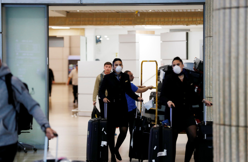Airline employees wearing masks walk in the arrivals terminal after Israel said it will require anyone arriving from overseas to self-quarantine for 14 days as a precaution against the spread of coronavirus, at Ben Gurion International airport in Lod, near Tel Aviv, Israel March 10, 2020 (photo credit: REUTERS/RONEN ZEVULUN)