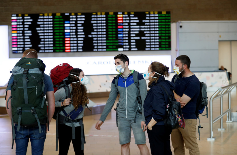 Travelers wearing masks chat in the arrivals terminal after Israel said it will require anyone arriving from overseas to self-quarantine for 14 days as a precaution against the spread of coronavirus, at Ben Gurion International airport in Lod, near Tel Aviv, Israel (photo credit: REUTERS/RONEN ZEVULUN)
