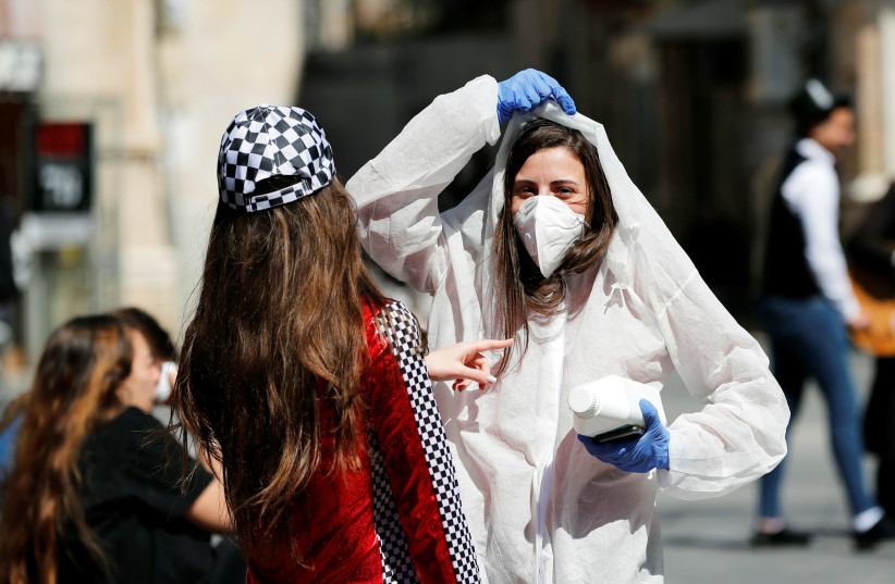 A teenager wears a costume as a reference to the coronavirus during the Jewish holiday of Purim, a celebration of the Jews' salvation from genocide in ancient Persia, as recounted in the Book of Esther. in Jerusalem March 8, 2020 (photo credit: REUTERS/Ronen Zvulun)