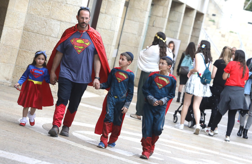 A Jewish father and his children wearing their Purim costumes, in this case, inspired by the fictional character of Superman   (photo credit: MARC ISRAEL SELLEM)