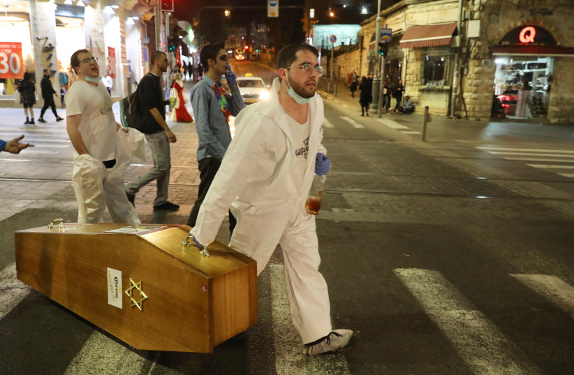 Jerusalem residents enjoy the holiday of Purim while wearing costumes that poke fun at the coronavirus pandemic, pretending to bury the virus (photo credit: MARC ISRAEL SELLEM)
