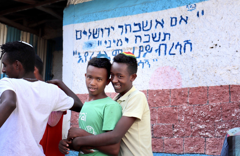 TWO BOYS before morning services at the Hatikva Synagogue in Gondar. In the back, the famous text reads: 'If I forget you, O Jerusalem, may my right hand forget [its skill].' (photo credit: CARMEL MADASHAHI)
