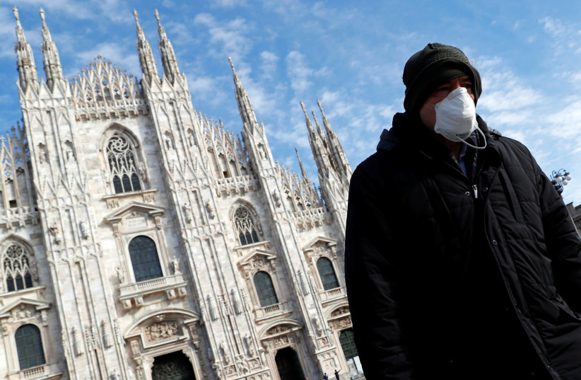 A man wearing a protective face mask to prevent contracting the coronavirus walks past the Duomo Cathedral in Milan, Italy, March 4, 2020 (photo credit: GUGLIELMO MANGIAPANE / REUTERS)