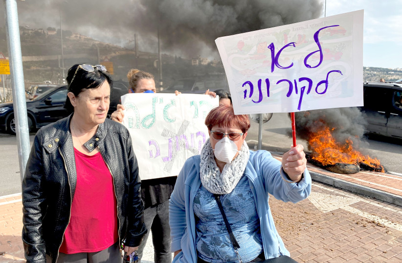RESIDENTS HOLD placards (this one reads 'No to corona') as they demonstrate against a report that Israel may quarantine visitors from South Korea at a military base in Har Gilo, on February 23.  (photo credit: REUTERS)