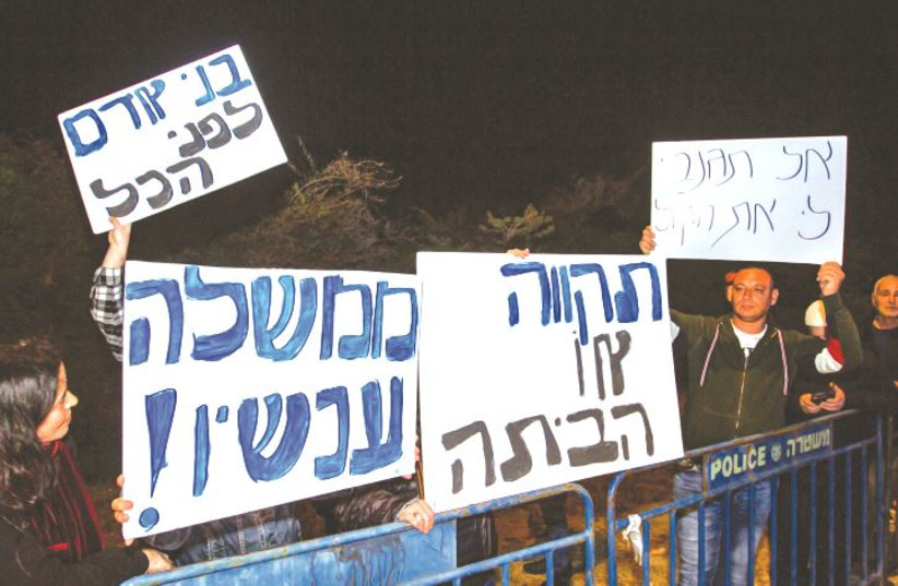 PROTESTERS STAND outside the Kibbutz Reshafim home of Gesher Party leader Orly Levy-Abecassis Wednesday night, following her decision not to support a Joint List-backed minority government.  (photo credit: FLASH90)