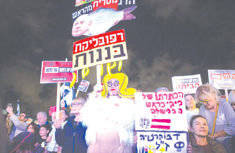 PROTESTERS AT HABIMA Square in Tel Aviv last November call on Netanyahu to quit, following the announcement by Attorney-General Avichai Mandelblit that the prime minister would stand trial. (photo credit: MIRIAM ALSTER/FLASH90)