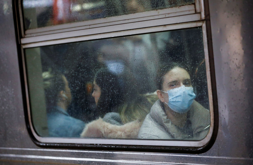 A woman wears a face mask on the subway as the coronavirus outbreak continued in Manhattan, New York City, New York, U.S., March 13, 2020 (photo credit: REUTERS/ANDREW KELLY)