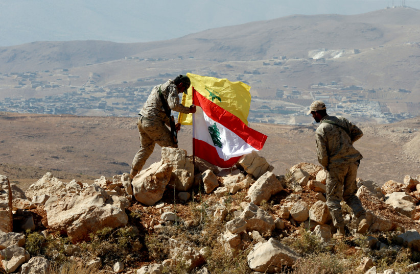 Hezbollah fighters put Lebanese and Hezbollah flags at Juroud Arsal, Syria-Lebanon border (photo credit: REUTERS)