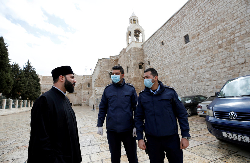 Palestinian police officers stand guard outside the Church of the Nativity that was closed as a preventive measure against the coronavirus, in Bethlehem in the West Bank March 6, 2020 (photo credit: REUTERS/MUSSA QAWASMA)