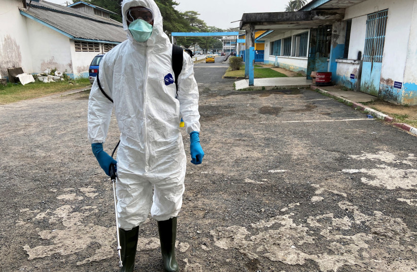 A medical staff wears protective gear at a new section specialised in receiving any person who may have been infected with coronavirus at The Quinquinie Hospital in Douala, Cameroon February 17, 2020 (photo credit: REUTERS/JOSIANE KOUAGHEU)
