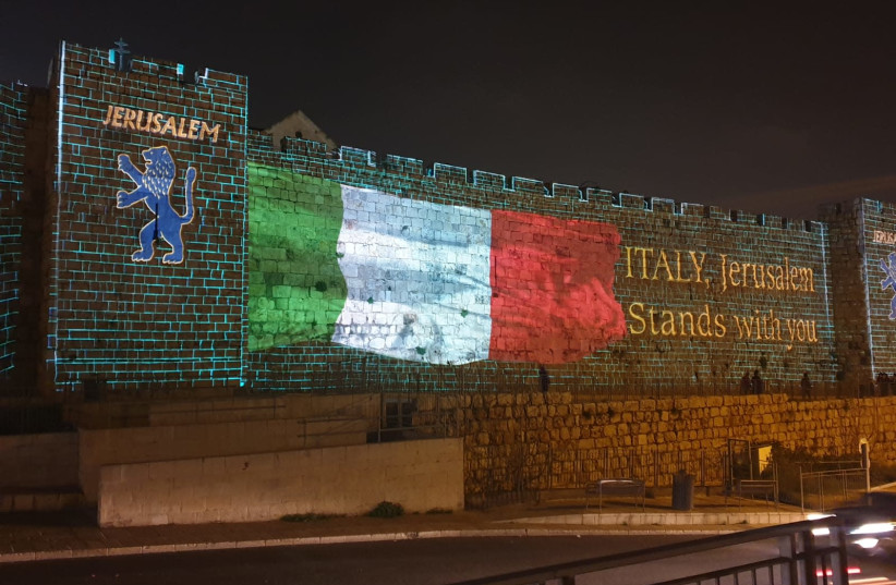 The Italian flag shown on the Old City walls of Jerusalem to show solidarity during the coronavirus outbreak (photo credit: ARNON BOSSANI)