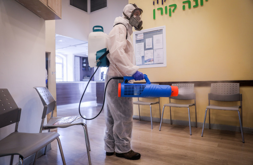 Workers wearing protective clothes disinfect a shop in Jerusalem, on March 15, 2020, as part of measures to prevent the spread of the Coronavirus. (photo credit: YONATAN SINDEL/FLASH90)