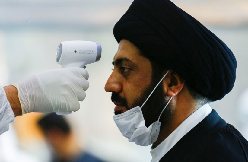A medical staff member in protective gear checks the temperature of a cleric man amid concerns over the coronavirus (COVID-19) spread, at Najaf airport in the holy city of Najaf upon his arrival from Iran, Iraq March 15, 2020. (photo credit: REUTERS/ALAA AL-MARJANI)