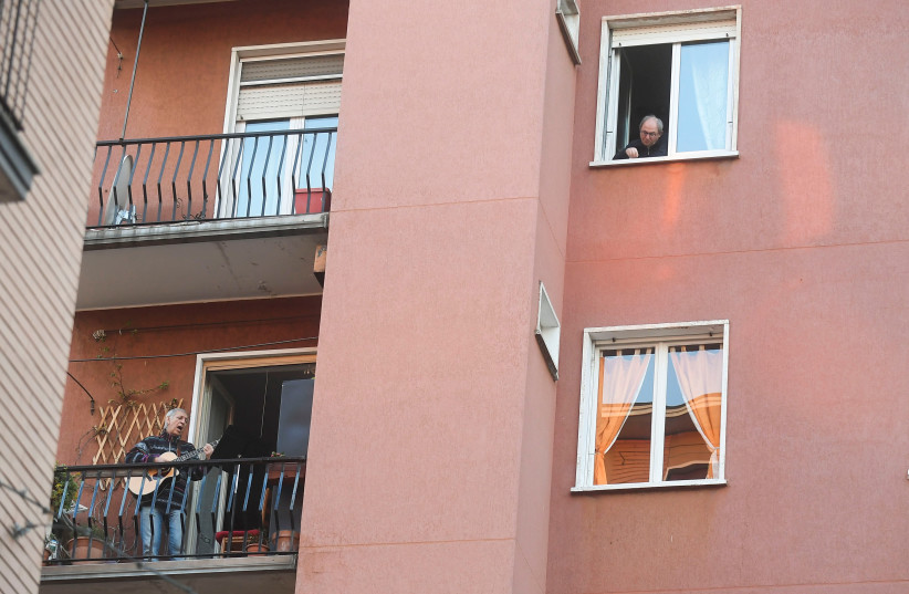 A man plays the guitar and sings from a balcony to raise morale on the sixth day of an unprecedented lockdown across of all Italy imposed to slow the outbreak of coronavirus in Milan, Italy March 15, 2020 (photo credit: DANIELE MASCOLO / REUTERS)