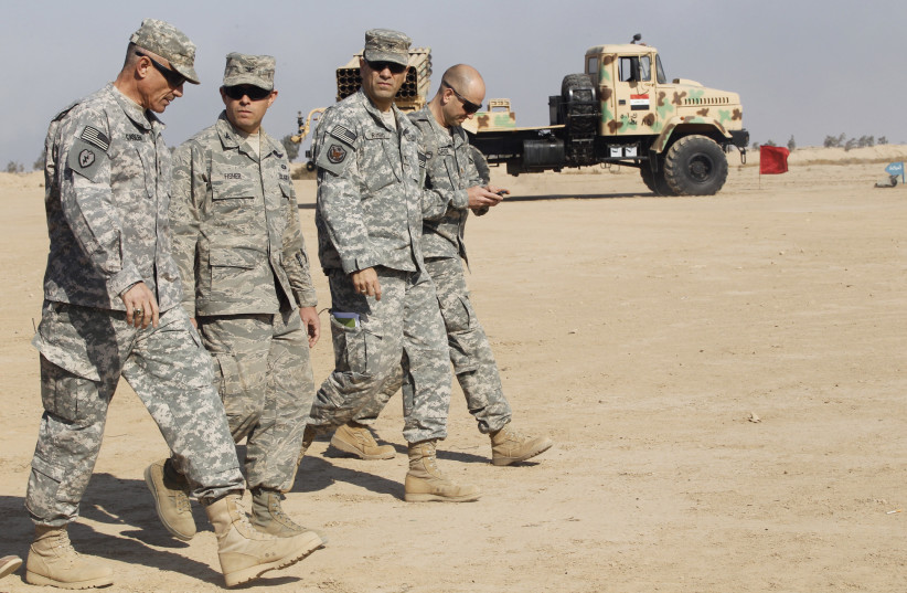 US soldiers walk near a rocket launcher missile at Basmaya military base in Baghdad (photo credit: REUTERS/MOHAMMED AMEEN)