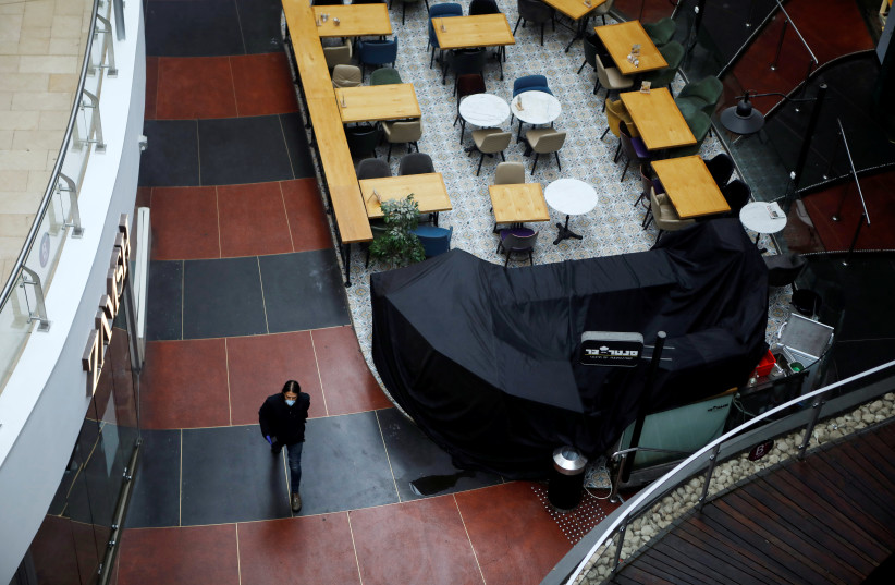 A man wearing a mask walks inside a shopping centre after Israeli Prime Minister Benjamin Netanyahu's government announced that malls, hotels, restaurants and theaters will shut down from Sunday, in an escalation of precautionary measures against coronavirus, in Tel Aviv, Israel March 15, 2020 (photo credit: REUTERS/NIR ELIAS)