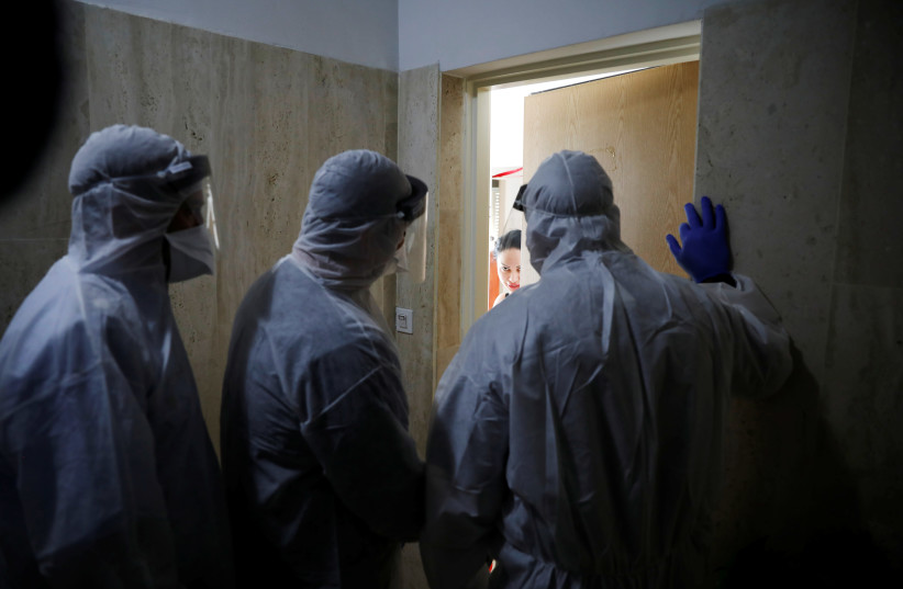Health Ministry inspectors speak with a woman who is in self quarantine as a precaution against coronavirus spread in Hadera (photo credit: REUTERS)