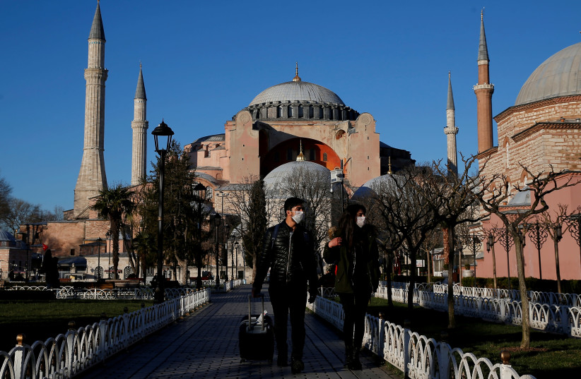 Tourists wearing protective face masks, due to coronavirus disease (COVID-19) concerns, stroll at Sultanahmet square in Istanbul, Turkey, March 17, 2020. (photo credit: REUTERS/KEMAL ASLAN)