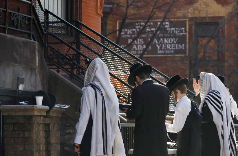 Hasidic Jewish men gather for a morning prayer outside of a synagogue, closed due to coronavirus disease (COVID-19), in South Williamsburg, Brooklyn, New York City, New York (photo credit: REUTERS)