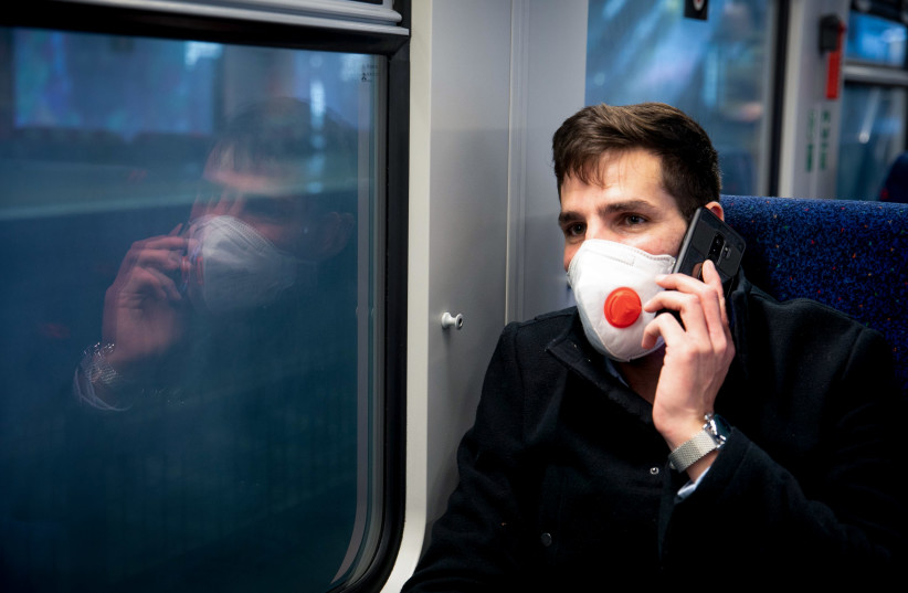 A man wears a face mask for fear of the coronavirus as he takes the train to Haifa, on March 17, 2020 (photo credit: YOSSI ALONI/FLASH90)