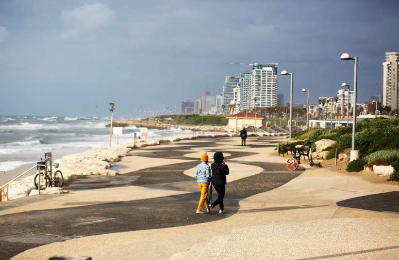 TWO PEOPLE walk near the beach in Tel Aviv (photo credit: REUTERS)