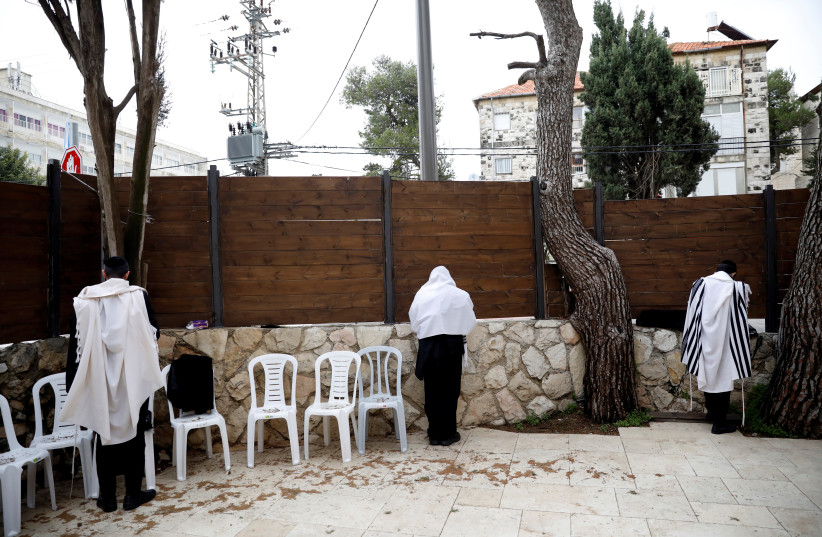 Jewish men wearing prayer shawls perform morning prayers in a courtyard of a synagogue in Jerusalem (photo credit: REUTERS)