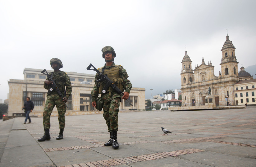 Members of the military walk in Bolivar Square during the four-day mandatory isolation decreed by the mayor of Bogota, as a preventive measure against the spread of the coronavirus disease (COVID-19), in Bogota, Colombia March 20, 2020. (photo credit: REUTERS)