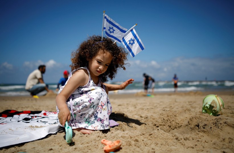A girl plays on the beach as Israel celebrates its Independence Day marking the 71st anniversary of the creation of the state, in Tel Aviv, Israel May 9, 2019 (photo credit: REUTERS/CORINNA KERN)
