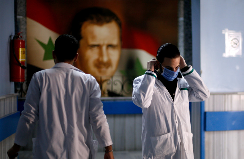 A health worker with a face mask walks inside a hospital in Syria (photo credit: REUTERS/OMAR SANADIKI)