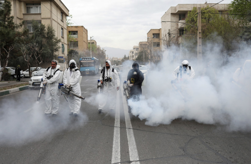 Members of firefighters wear protective face masks, amid fear of coronavirus disease (COVID-19), as they disinfect the streets, ahead of the Iranian New Year Nowruz, March 20, in Tehran, Iran March 18, 2020. (photo credit: WANA NEWS AGENCY/REUTERS)