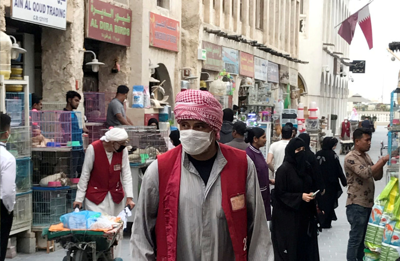 A man wears a protective face mask, following the outbreak of coronavirus, as he pushes a cart in souq Waqif in Doha, Qatar (photo credit: REUTERS)