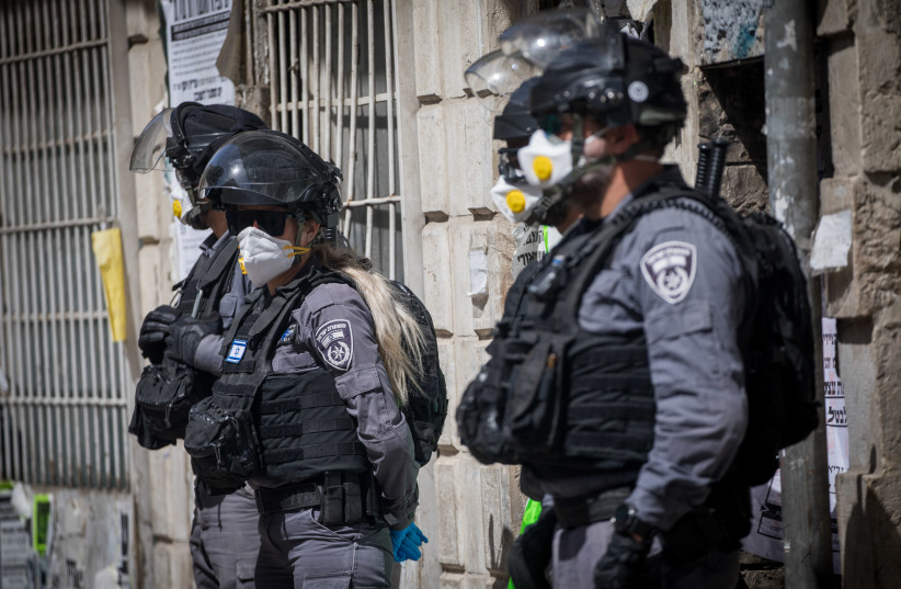 Israeli police officers seen during a raid on the ultra orthodox Jewish neighborhood of Meah Shearim, as they close shops and disperse public gatherings following the government decisions in an effort to contain the spread of the coronavirus. March 24, 2020 (photo credit: YONATAN SINDEL/FLASH90)