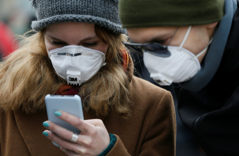 People wearing protective face masks use a smartphone on a street amid coronavirus (COVID-19) concerns (photo credit: REUTERS/VALENTYN OGIRENKO)