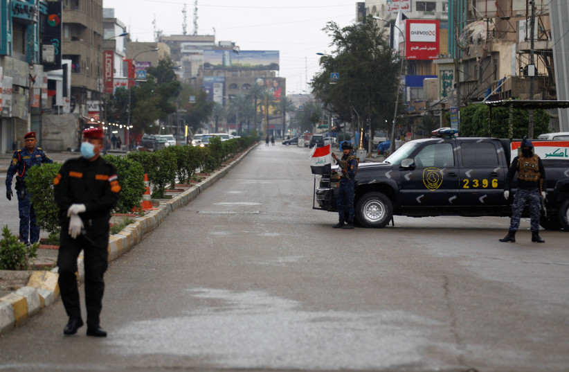 Iraqi security forces gather in a street, during a curfew imposed to prevent the spread of coronavirus disease (COVID-19), in Baghdad, Iraq (photo credit: REUTERS/KHALID AL MOUSILY)