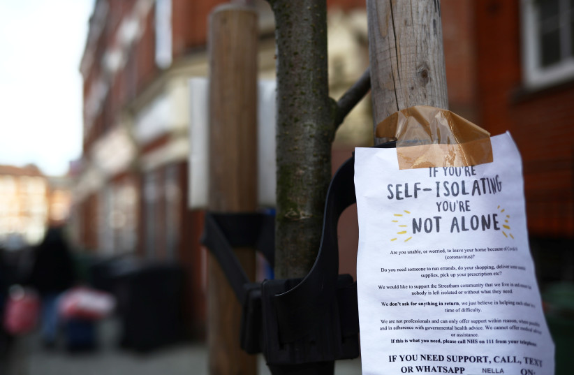 A sign is seen down a London street regarding self isolation as the spread of the coronavirus disease (COVID-19) continues. London, Britain March 21, 2020 (photo credit: HANNAH MCKAY/ REUTERS)