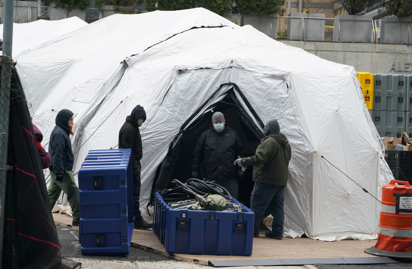 Workers construct what is believed to be a makeshift morgue behind a hospital during the outbreak of coronavirus disease in New York City (photo credit: CARLO ALLEGRI/REUTERS)
