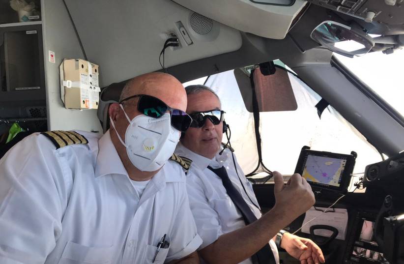 Pilots from the El Al flight returning with Israelis stranded in Colombia, wearing masks to prevent them from contracting the coronavirus. (photo credit: EL AL)