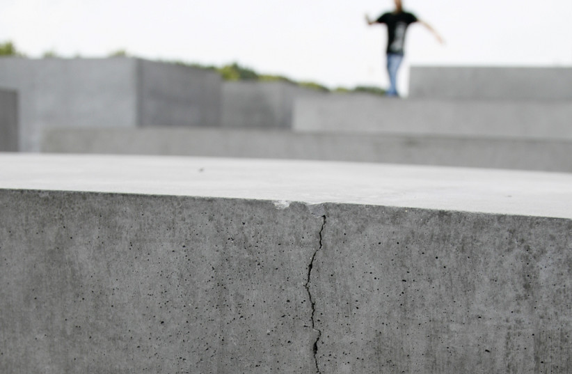 A MAN stands atop the concrete blocks of the Holocaust-Mahnmal memorial, many of which have cracks. The book says German Holocaust memorials are insufficient (photo credit: REUTERS)