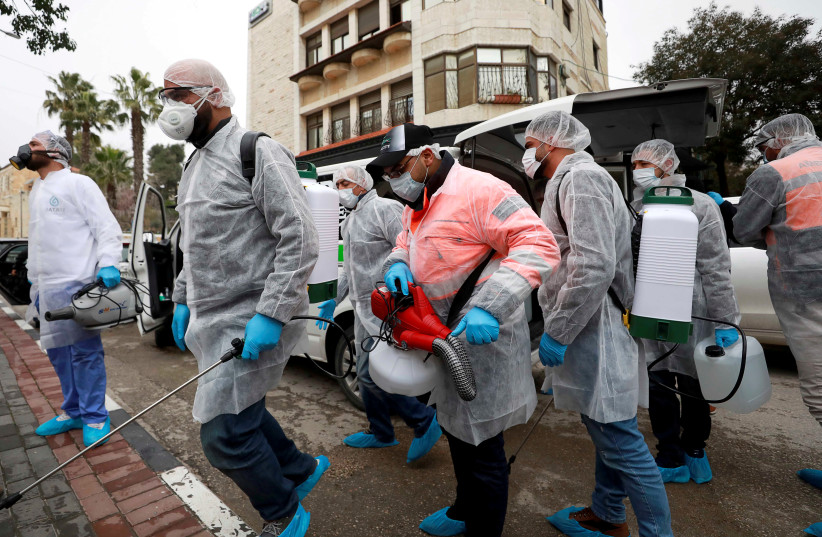 FILE PHOTO: Palestinian workers make their way to disinfect religious sites as preventive measures against the coronavirus, in Ramallah in the in the West Bank March 7, 2020 (photo credit: REUTERS/MOHAMAD TOROKMAN/FILE PHOTO)