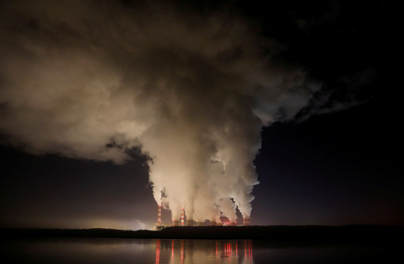 Smoke and steam billows from Belchatow Power Station, Europe's largest coal-fired power plant operated by PGE Group, at night near Belchatow, Poland December 5, 2018. (photo credit: REUTERS)