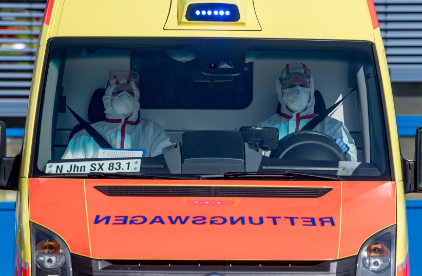 An ambulance car carries an Italian patient infected with coronavirus arrives at the Helios hospital in Leipzig, Germany, March 25, 2020, as the spread of the coronavirus disease (COVID-19) continues (photo credit: HENDRIK SCHMIDT/POOL VIA REUTERS)