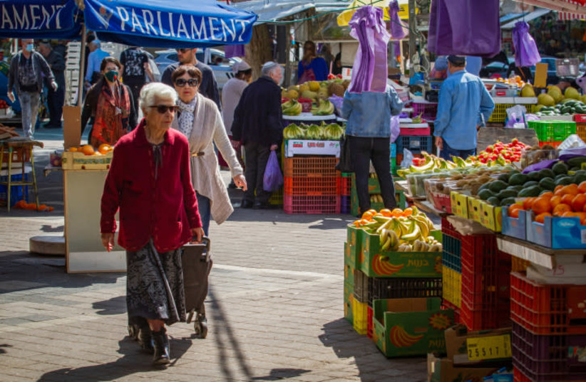 OLDER PEOPLE shop at the market in Netanya on Wednesday. The government ordered all bars, restaurants, malls and markets to close, in an effort to contain the spread of the coronavirus.  (photo credit: FLASH90)