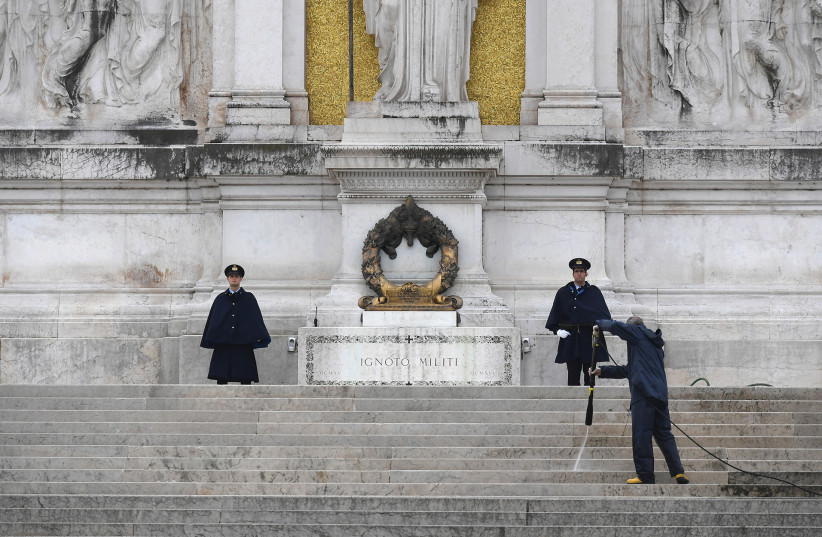 A MAN disinfects stairs leading to the monument in honor of unknown soldiers at Piazza Venezia as Italy tightened measures to try and contain the spread of coronavirus, in Rome on Saturday. (photo credit: REUTERS)