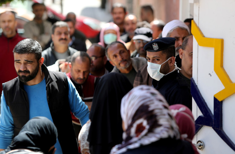 A policeman, wearing a mask as a precaution against the coronavirus disease (COVID-19), stands guard as Palestinians wait outside a bank to withdraw cash, in Gaza City March 29, 2020 (photo credit: REUTERS/MOHAMMED SALEM)